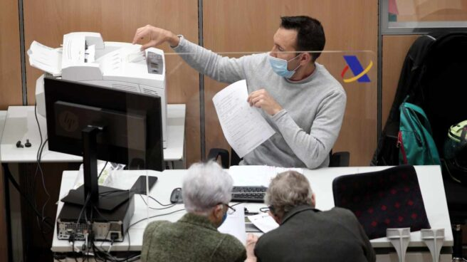 Un funcionario atiende a dos contribuyentes en una oficina de la Agencia Tributaria.