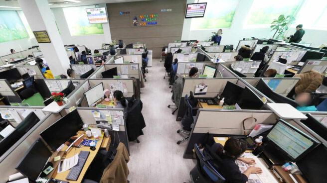 Trabajadores de un call center reciben las llamadas de clientes en una jornada laboral
