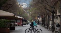 Un trabajador de Deliveroo en bicicleta por una calle de Barcelona.