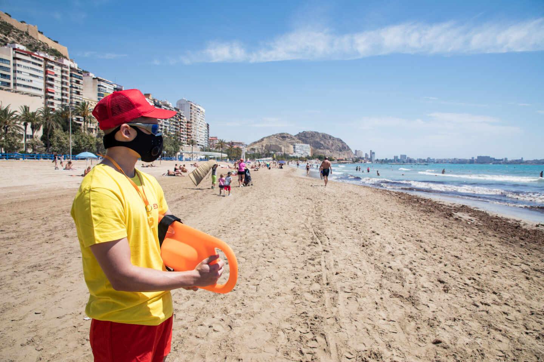 Un socorrista protegido con mascarilla vigila la Playa del Postiguet, en Alicante.