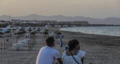 Dos jóvenes sentados contemplan la playa de la Malvarrosa, en Valencia.