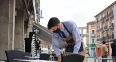Un camarero desinfecta una de las mesas de su establecimiento