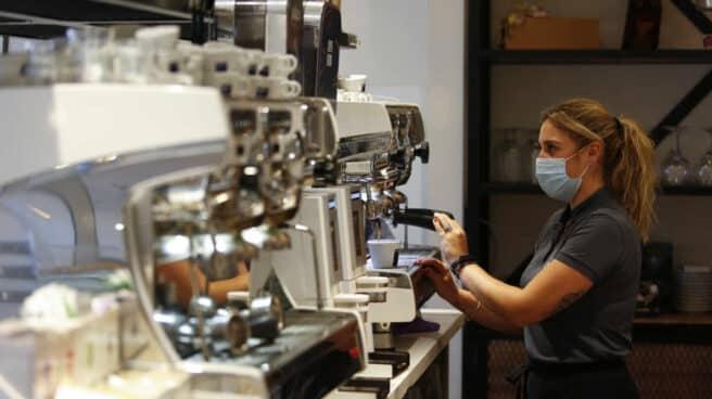 Una camarera sirviendo café en un bar.