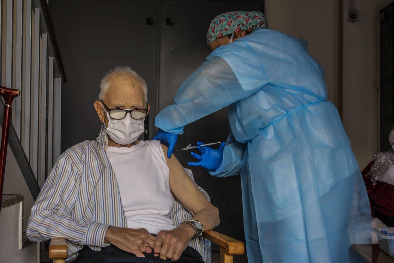 Un anciano es vacunado contra el coronavirus por una sanitaria en Valencia.