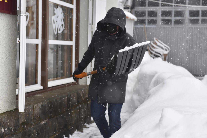 Un hombre aparta la nieve con una pala en el Pirineo aragonés, en Huesca.