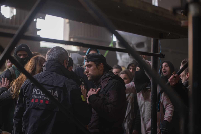 Un Mosso d'Esquadra frente a varios de los participantes en la 'rave'