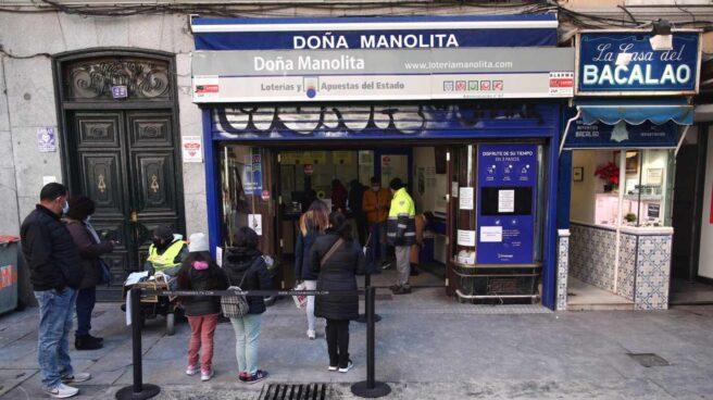 Varias personas hacen cola ante la administración de lotería Doña Manolita, en Madrid.