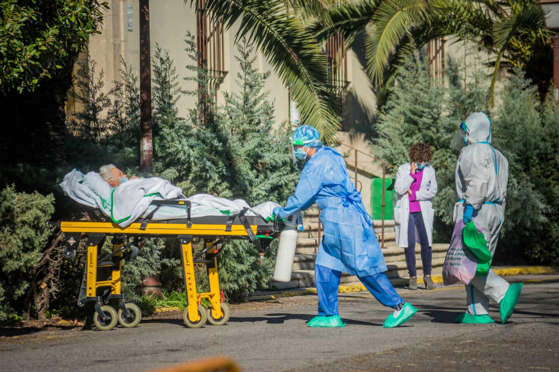 Sanitarios trasladan en camilla a un enfermo de Covid-19 al Hospital Virgen de la Montaña de Cáceres, Extremadura
