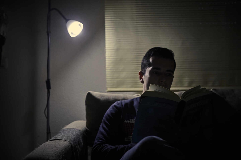 Un chico lee un libro bajo la luz de una lámpara en Madrid.