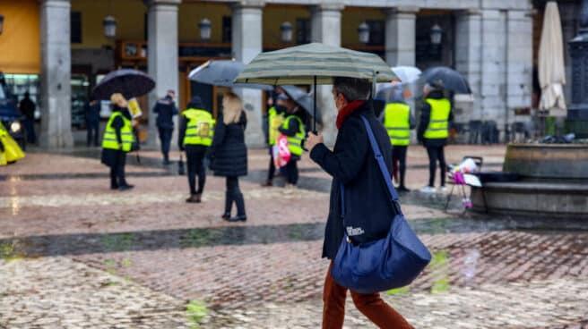Una mujer camina protegida por un paraguas en la Plaza Mayor de Madrid.