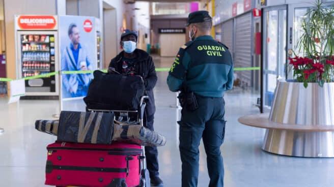 Agentes de la Guardia Civil y empleados de seguridad vigilan a los pasajeros en el interior del Aeropuerto de Ibiza.