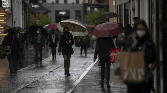 Varias personas con paraguas en una calle céntrica de Sevilla.