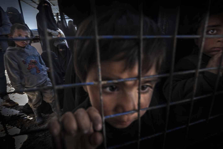 Un niño sirio observa a través de una verja en un campo de refugiados