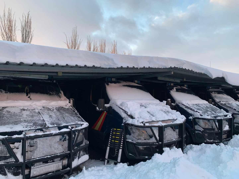 Vehículos de la UIP de Madrid, cubiertos de nieve este fin de semana en la base de Moratalaz (Madrid).