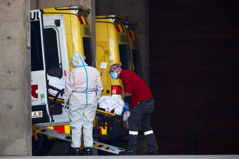 Dos profesionales sanitarios trasladan a un paciente en el hospital de Bellvitge