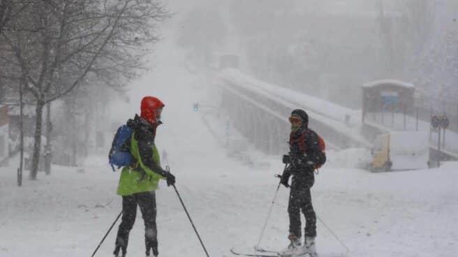 Viandantes esquían por una calle cubierta de nieve en Madrid.