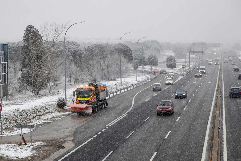 Una quitanieves lista para trabajar, mientras varios vehículos circulan por la A5 a la entrada de Madrid.