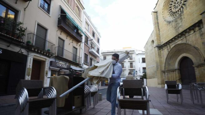 Un trabajador recoge el mobiliario de la terraza en Córdoba.