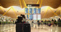 Dos viajeros señalando un panel de vuelo en la terminal T4 del Aeropuerto Adolfo Suárez Madrid-Barajas