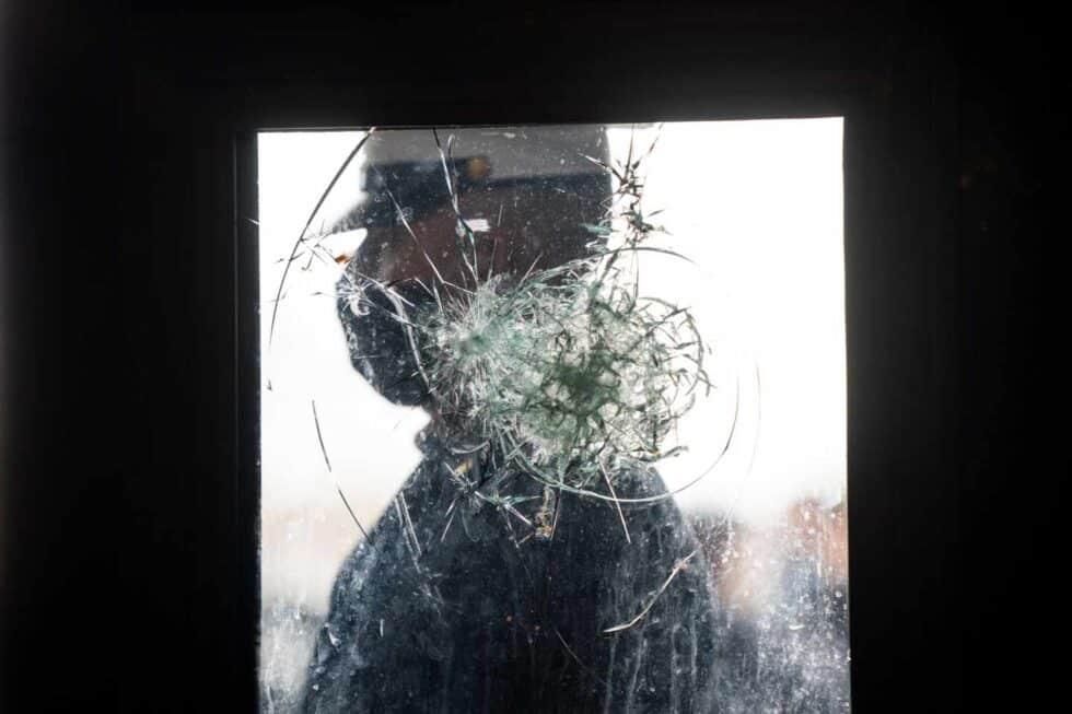 Un marine hace guardia este lunes tras el cristal de una puerta que resultó dañado durante el asalto al Capitolio.