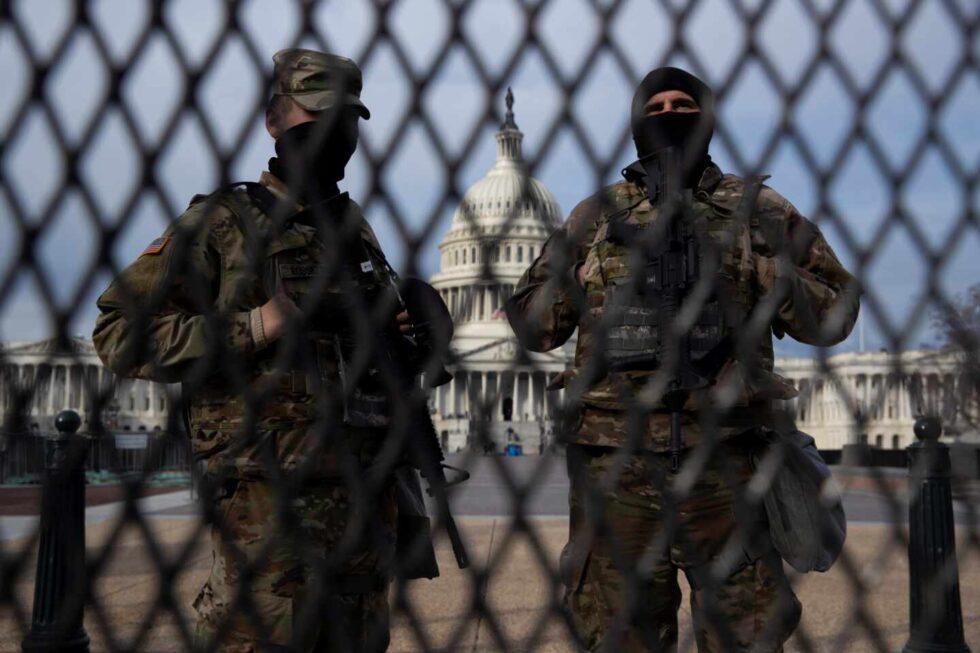 Miembros de la Guardia Nacional vigilan tras una valla en el Ala Este del Capitolio de los Estados Unidos.