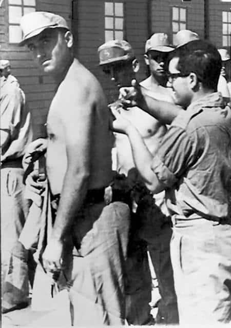 Un recluta recibe una vacuna en el omóplato durante el servicio militar.