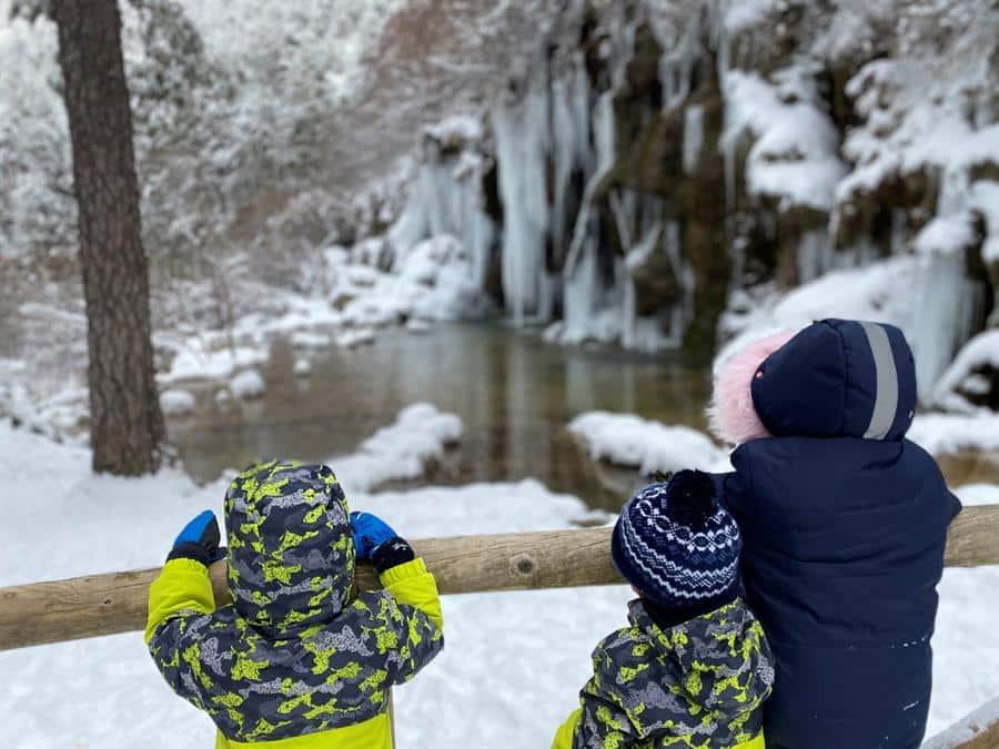 Varios niños observan el nacimiento del río Cuervo.