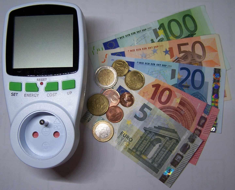 Imagen de un potenciador de luz junto a varios billetes de euros y algunas monedas