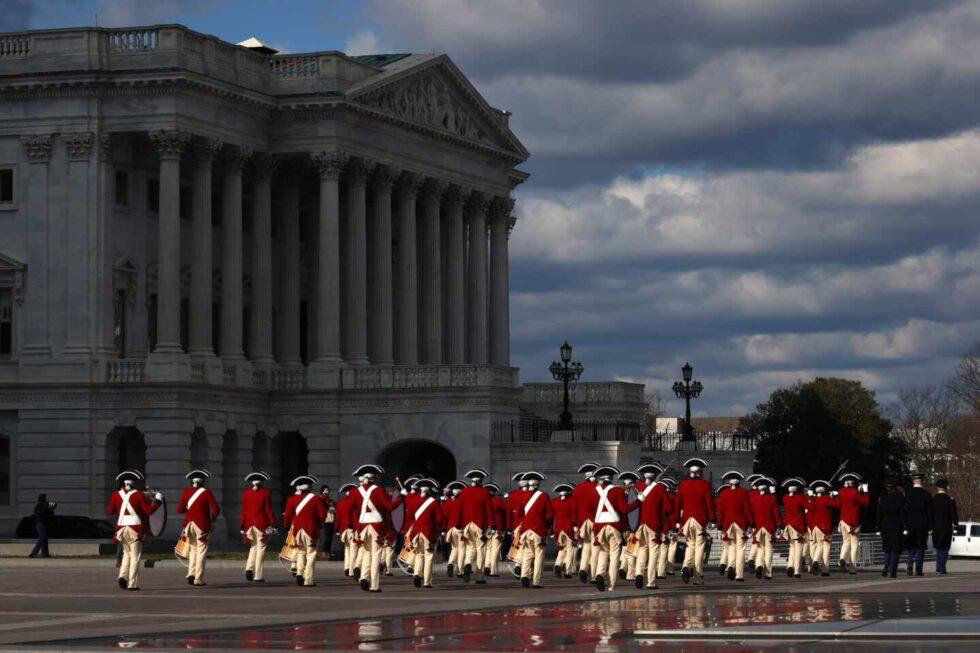Tropas con trajes de época del siglo XVIII marchan por el frente este del Capitolio durante un ensayo de inauguración frente al Capitolio en Washington