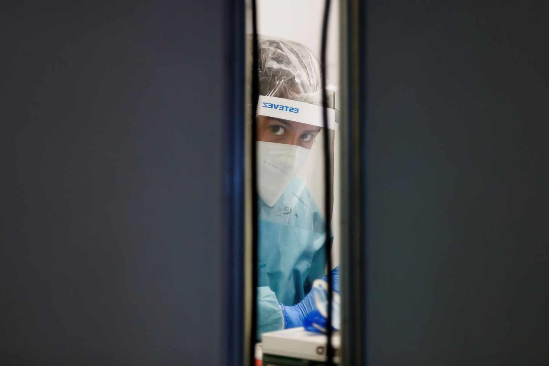 Un médico se asoma por la puerta de una sala de un aeropuerto donde toma muestras.