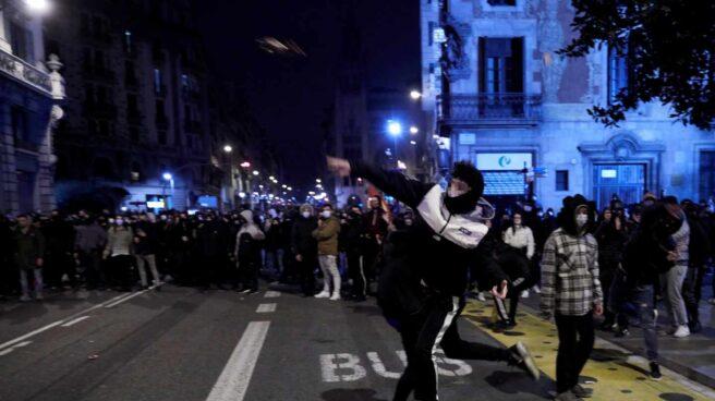 Manifestantes lanzan objetos esta noche frente a la comisaría de Vía Layetana, en el centro de Barcelona, en una nueva manifestación por la libertad de Pablo Hasel, después de cinco días consecutivos de protestas que han finalizado con enfrentamientos con los Mossos d'Esquadra y daños a bienes públicos y privado.