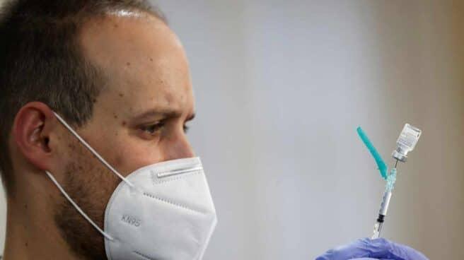 Un sanitario prepara una vacuna.