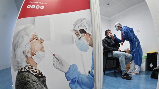 Una sanitaria hace una PCR a un paciente