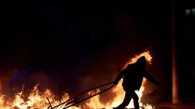 Un manifestante lanza una valla a la barricada en llamas en la calle Aragó, anoche en Barcelona durante las protestas por la detención de Pablo Hasél.