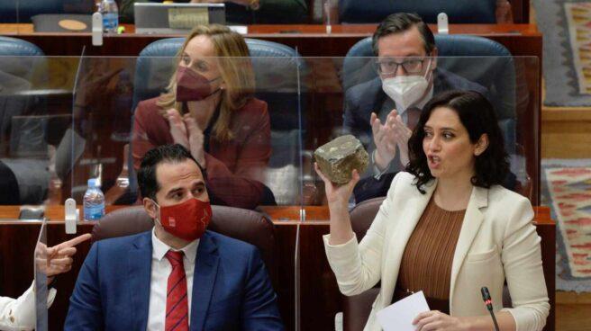 Isabel Díaz Ayuso enseña un adoquín en la Asamblea de Madrid.