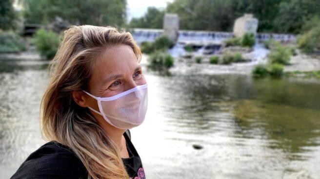 Una mujer con una mascarilla transparente de rejilla