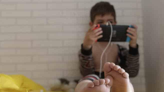 Un niño pequeño confinado juega con una tablet en su habitación