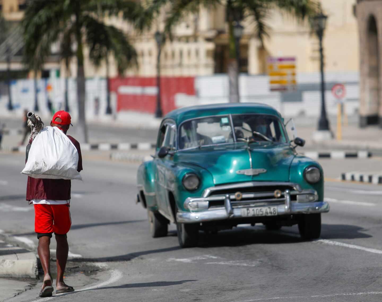 Un automóvil pasa por una calle habanera