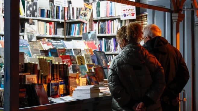 Dos personas ojean libros en un puesto callejero de libros
