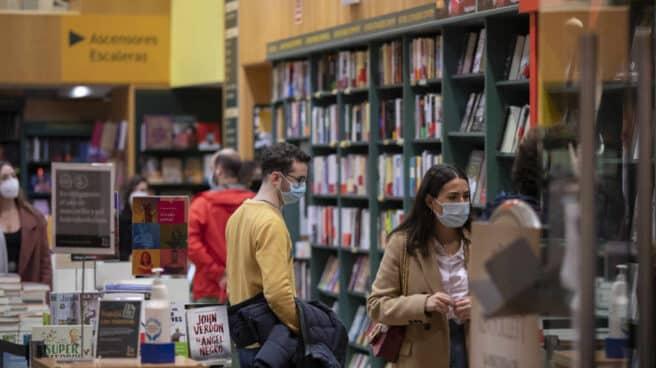 Personas consultan las estanterías de una librería