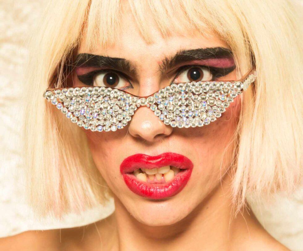Samantha Hudson con una peluca rubia, los labios pintados, y unas gafas de sol con brillantina