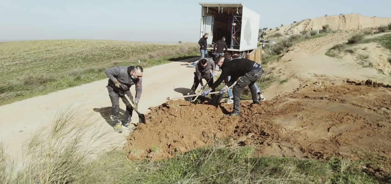 Trabajadores de producción con material de excavación en sus manos en un terreno