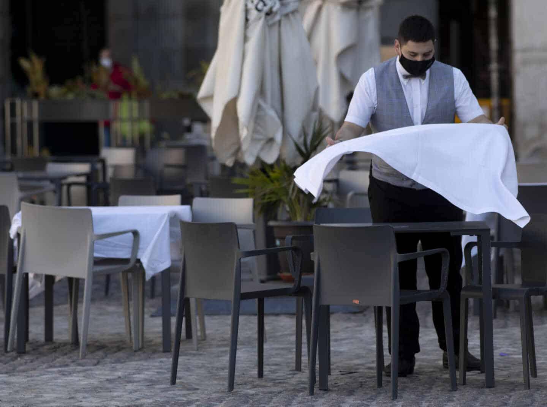 Un camarero prepara la mesa de una terraza de un establecimiento ubicado en la Plaza Mayor