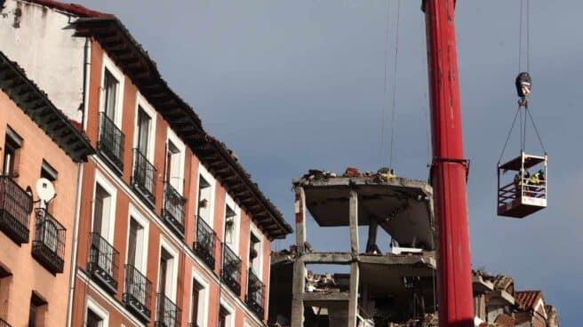 Un grúa durante el desmontaje del edificio siniestrado en el número 98 de la calle Toledo, en Madrid