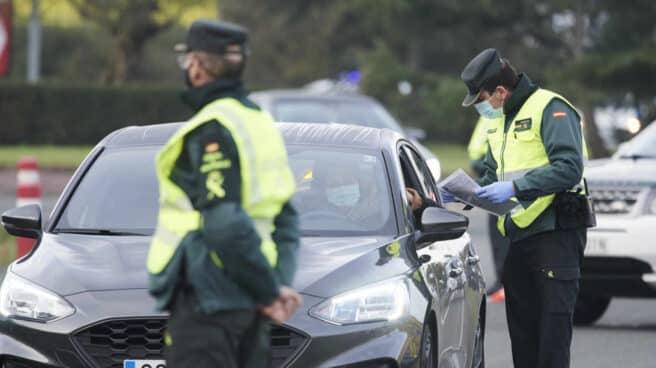 Un agente de la Guardia Civil pide la documentación a un vehículo durante un control efectuado en Laredo, Cantabria.