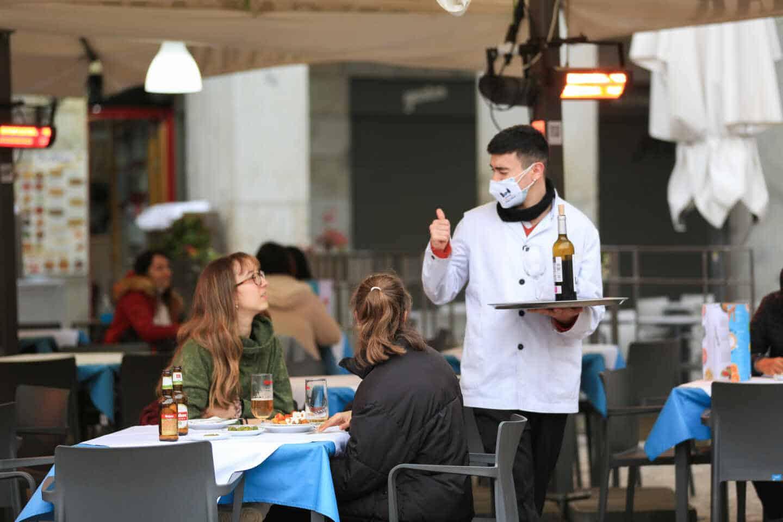 Un camarero atiende a dos clientas en la terraza de un bar en el centro de Madrid