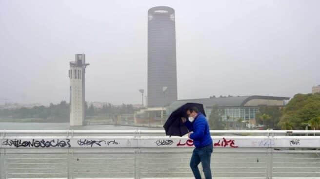 Un persona se protege de la lluvia y el viento caminando por Sevilla.