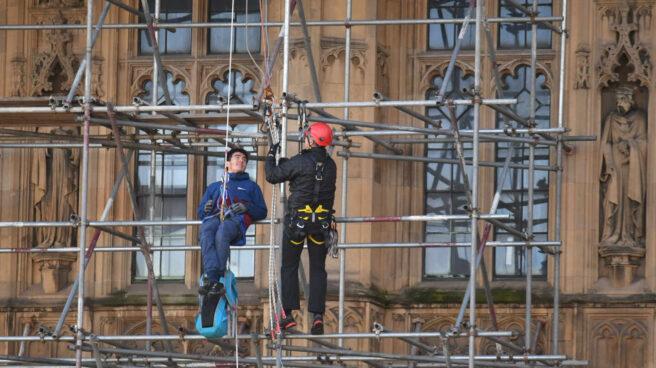 Unos trabajadores en unos andamios de una fachada