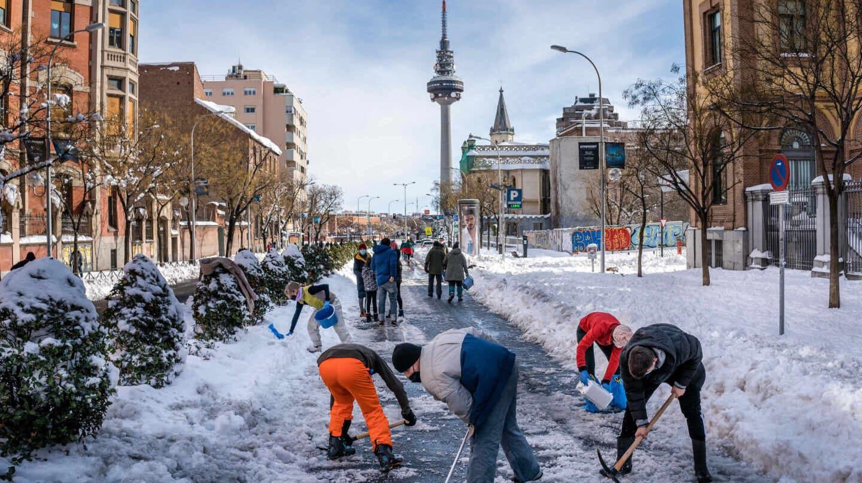 Madrileños limpian de nieve la calle