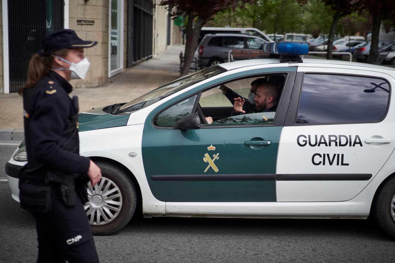 Una policía pasa junto a un patrullero de la Guardia Civil.